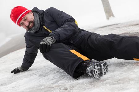 neige qui tombe: L'homme a un accident dans une rue glacée