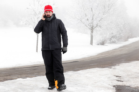 overthrow: Man with mobile phone is walking across the icy street Stock Photo