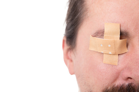 sightless: man´s eye glued medical plaster, isolated on white, concept first aid and sightless
