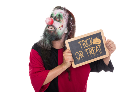 scary clown: scary Clown holding a sign, text Trick or treat, isolated on white, concept Halloween and Party