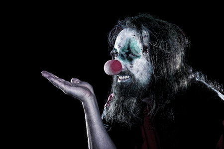 psychopath: horror clown with ugly face looking to copyspace, black background, concept creepy theme party or halloween