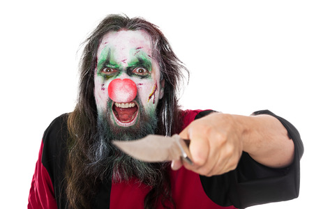 evil clown: evil clown threatening the beholder with a knife, isolated on white, concept scary halloween