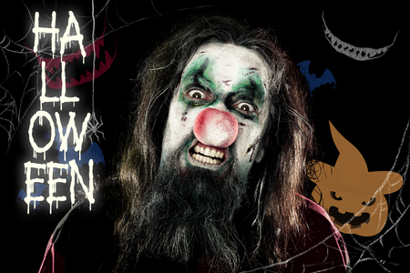 bared teeth: scary clown in front of a black background with a pumpkin and teeth, Text Halloween with a spider Stock Photo