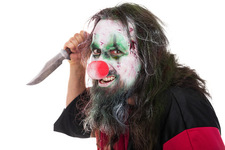 murderer: evil and scary clown holding a knife, isolated on white, concept horror and murderer