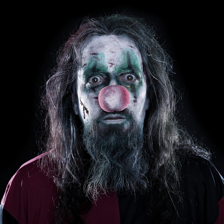 evil clown: Portrait of a creepy and bloody clown in front of black background, concept Horror or Halloween Stock Photo