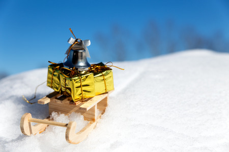 little bell: sledge with little gifts and bell in the snow, concept christmas presents Stock Photo
