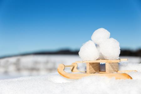 palle di neve: poco slitta con le palle di neve in mezzo alla neve, il concetto valanga lotta durante la stagione invernale
