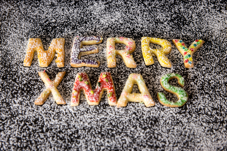 icing sugar: colorful christmas cookies, building the words Merry xmas, icing sugar on a black stone