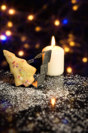 sugar cookie: Christmas card with christmas tree Cookie, Cookie cutter and a candle, icing sugar on black stone, sparkle background