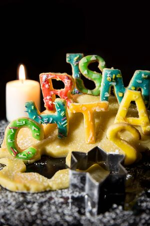 cookie cutter: Cookie letters, cookie dough, a candle and icing sugar, word Christmas in front of black background Stock Photo