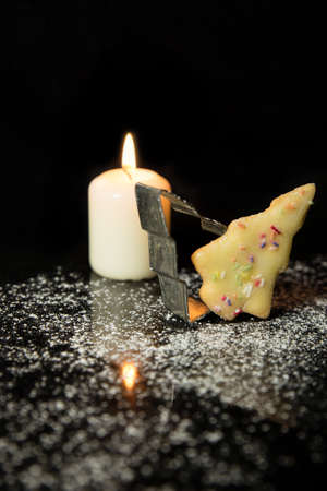 sugar cookie: Christmas card with christmas tree Cookie, Cookie cutter and a candle, icing sugar on black stone, black background