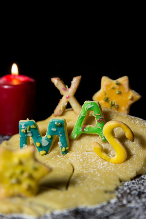 icing sugar: Cookie letters, cookie dough, a candle and icing sugar, wort xmas you in front of black background, concept christmas Stock Photo