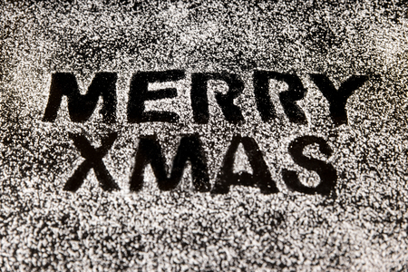 icing sugar: icing sugar on a black stone, text Merry xmas, concept christmas and bakery Stock Photo