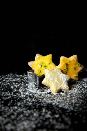 icing sugar: festive christmas card, star cookies and icing sugar, black stone, black background with copyspace