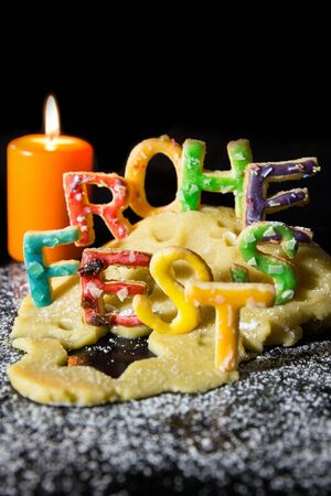 icing sugar: Cookie letters, cookie dough, a candle and icing sugar, german text in front of black background, concept christmas