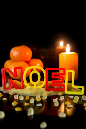 cookie cutter: Cookie cutter building the word noel, tangerines and candle, black background, concept christmas
