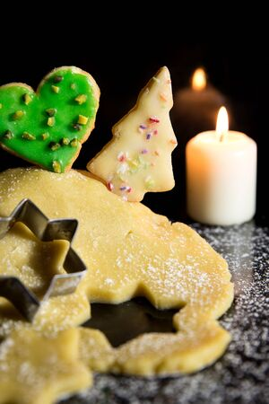icing sugar: cookie dough and cookies, candle and icing sugar in front of a black background, concept winter and christmas