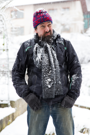chagrin: a wary man standing in a snowy garden Stock Photo