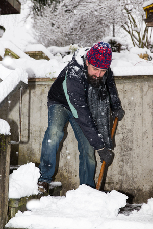 shoveling: caucasian man is snow shoveling the stairs