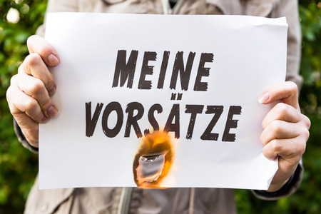 german: Woman is holding a burning paper with german text meine vorsaetze, means my resolutions