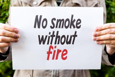 oracion: La mujer est� sosteniendo un papel con la frase, no hay humo sin fuego Foto de archivo