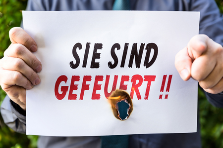 you are fired: Businessman is holding a burning paper with german text sie sind gefeuert, means you are fired