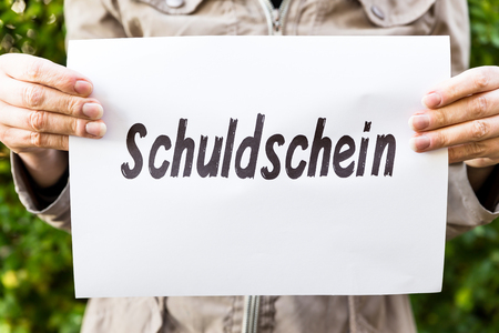 poverty relief: Woman is holding a paper with german word schuldschein, means debt Stock Photo