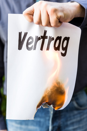 broken contract: businessman is holding a burning paper with german word vertrag, means contract