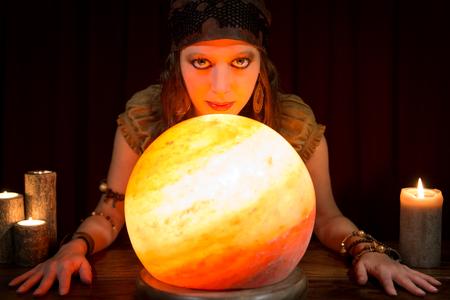 adivino: joven adivino bastante con una bola de cristal brillante y velas, el concepto de futuro y de entrenamiento
