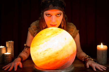 diviner: young pretty fortune teller with a shining crystal ball and candles, concept future and coaching