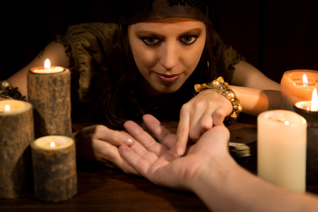 psychic reading: female fortune Teller is reading the lifeline and heart line, concept palmistry