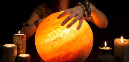 bonne aventure: Mains d'une diseuse de bonne aventure féminine, une boule de cristal brillant et bougies