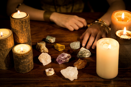 psychic: a lot of healing stones, candles and fortune teller hands, concept life coaching