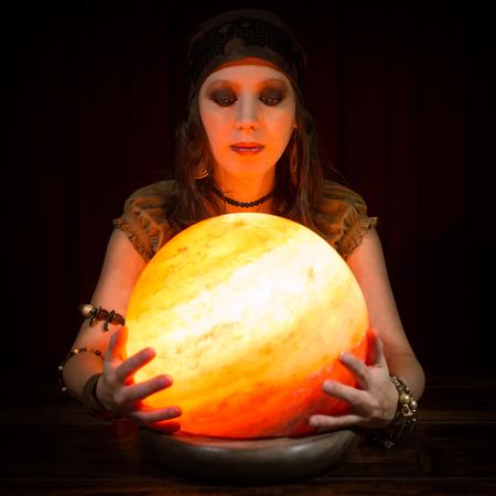 adivino: Hembra bonita joven que adivino con una bola de cristal, fondo oscuro Foto de archivo