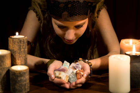 soothsayer: young female psychic with a lots of healing stones Stock Photo