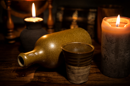 antik: beautiful medieval background with a old bottle, a mug and candles Stock Photo