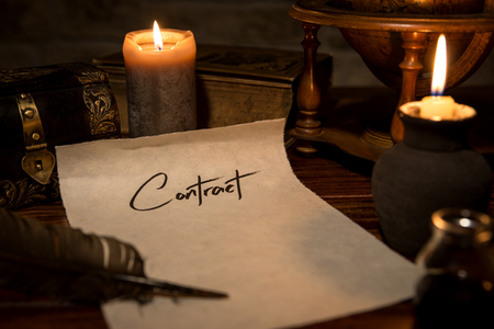 old desk: a parchment paper with a quill and ink, candles and medieval decoration, concept contract
