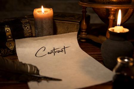 un papel de pergamino con una pluma y tinta, velas y la decoración medieval, contrato concepto