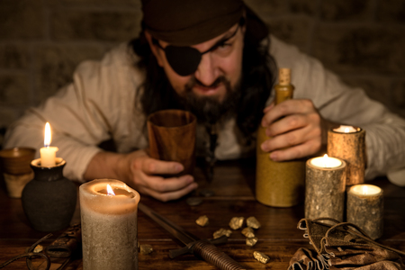 grumpy pirate with a bottle of rum sitting on a medieval table with a lot of candles
