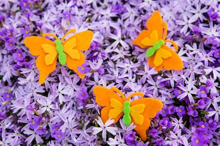 moos: orange felt butterflies atop a sea of purple blossoms Stock Photo