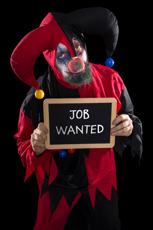 job market: sadly clown holding a slate with text job wanted, concept unemployed and job market, black background