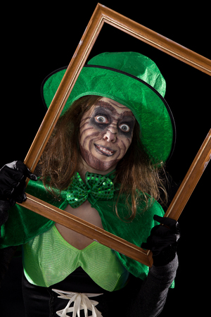 madly: a madly leprechaun behind a wooden frame, black background
