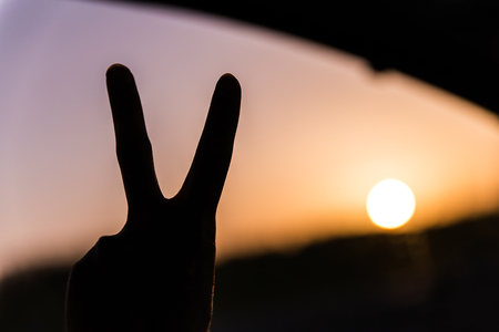 man showing the peace sign in front of a sunset Stock Photo