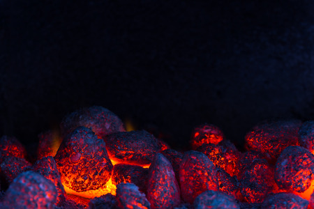 wood burning: glowing coal on a barbecue, closeup with copyspace at the top