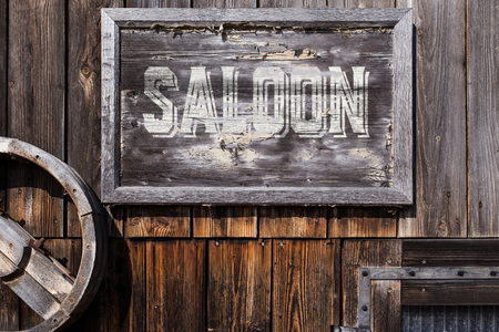 wooden sign with word saloon, planks on the background, vintage style Foto de archivo