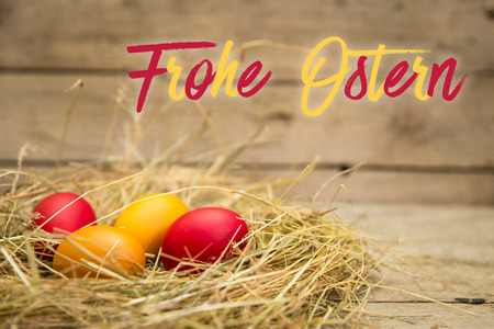 Ostern: easter nest with german text frohe ostern, which means happy easter. wooden background