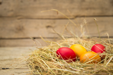 huevo: easter nest with yellow and red eggs, wooden background