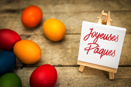 french text: colorful easter eggs with canvas and french text, joyeuses paques, which means happy easter, wooden background