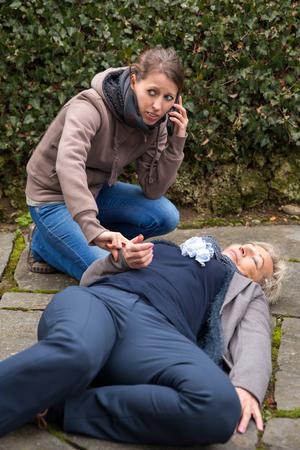derrumbe: altos de adultos está tumbado en el suelo, mujer joven hace una llamada de emergencia Foto de archivo