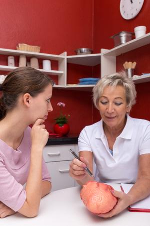 estetoscopio corazon: médico hembra madura está explicando un corazón humano a una mujer joven en una cirugía Foto de archivo